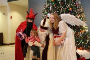 Three people in a devil, santa claus, and angel costumes